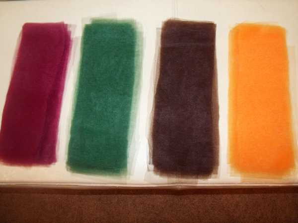 four piles of cut tulle rectangles: maroon, green, brown, and orange