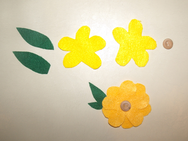 pieces of felt shaped like yellow flowers and green leaves