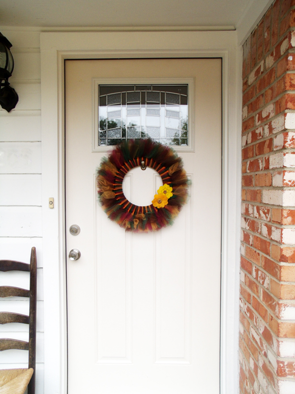 front porch with white siding and orange brick with a tulle wreath hanging on a white front door