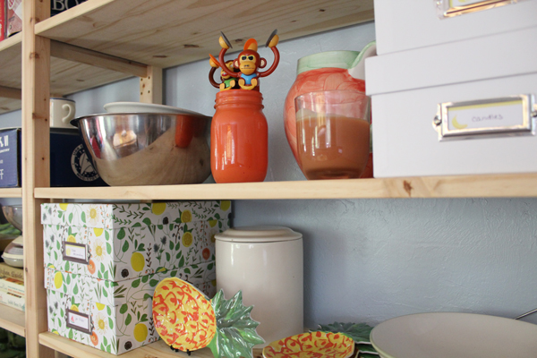 pine shelf cluttered with mismatched dishes, boxes, toys
