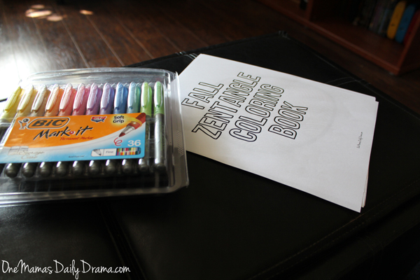 zentangle coloring book on a dark colored table beside a package of colorful markers