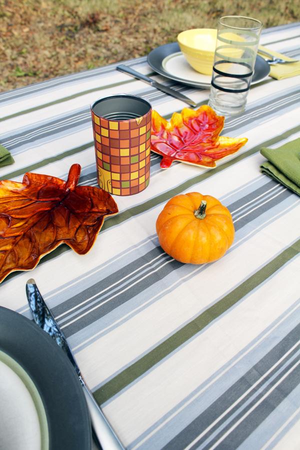 a mini pumpkin sits on a striped tablecloth beside a place setting