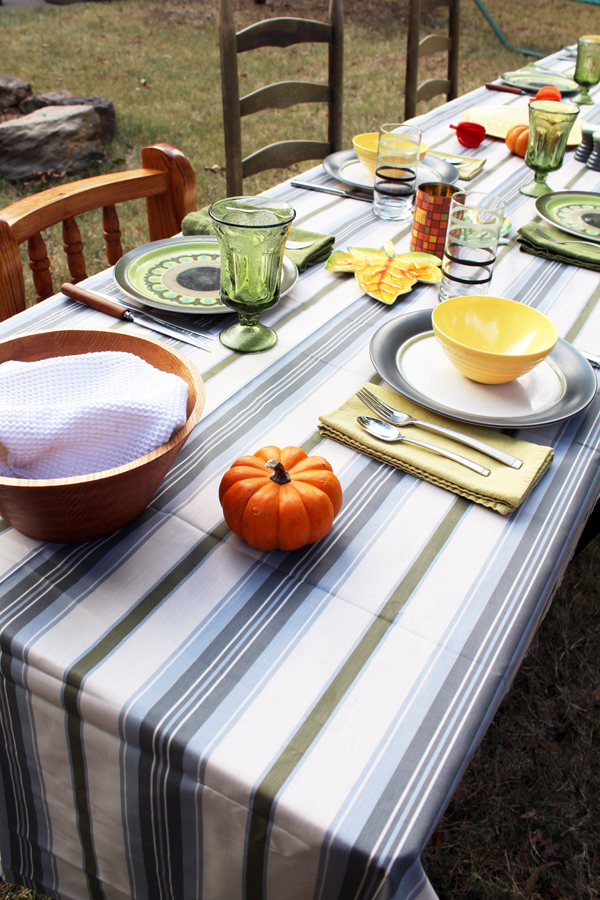 table setup for Thanksgiving dinner with a piece of green and white striped fabric for a cover