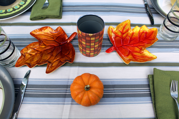 orange and brown paper-wrapped can with a tea light inside sitting on a striped tablecloth