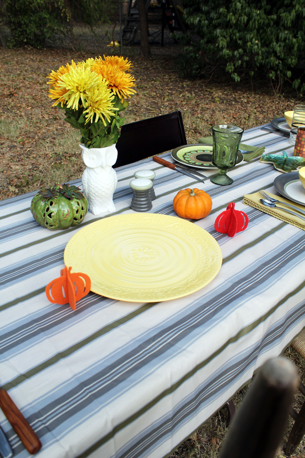 table with yellow serving tray and yellow and orange mums in a white owl-shaped vase