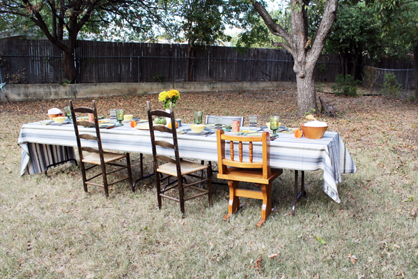 a long table with mismatched chairs outdoors