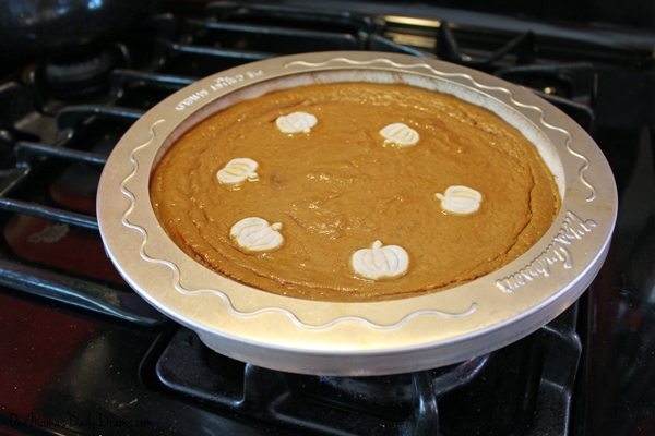 baking pumpkin pie with a pie shield covering the crust