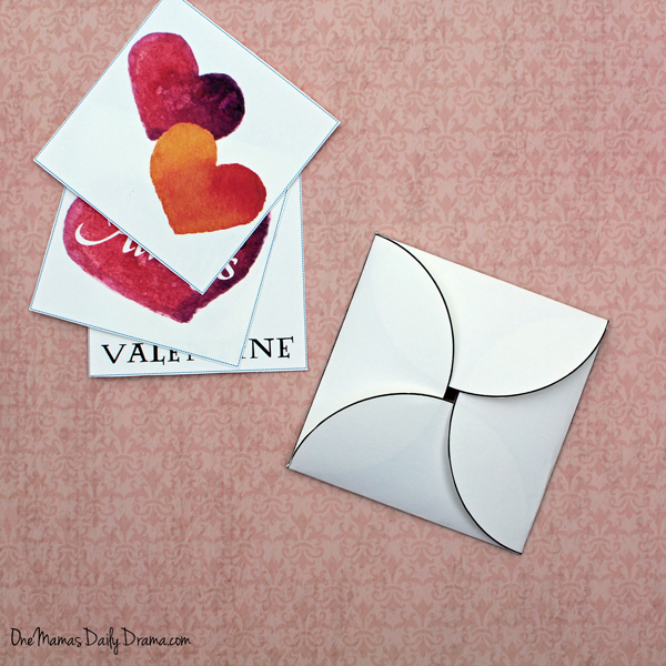 stack of 3 watercolor valentine cards beside a spiral folded envelope