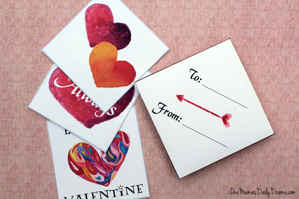 "closeup of valentine cards and a square envelope printed with ""to"" and ""from"" with lines for names"