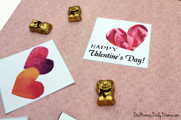 2 valentine cards on a pink surface sprinkled with chocolate bears wrapped in gold foil