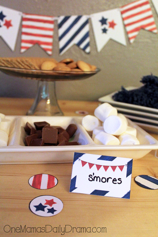 smores table tent card with ingredients on trays in the background