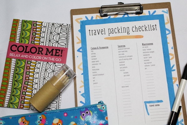 coloring book and pencils next to travel packing checklist
