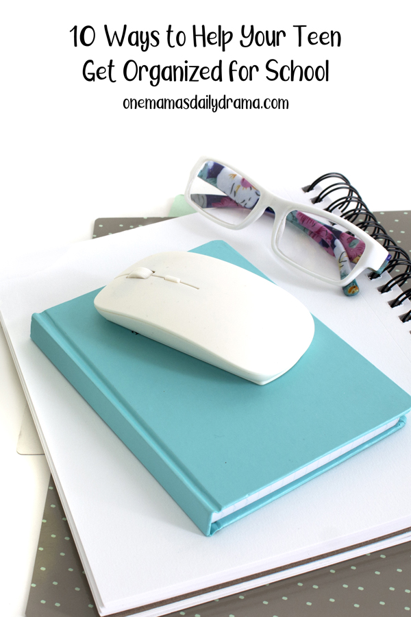 computer mouse and glasses sitting on a stack of notebooks