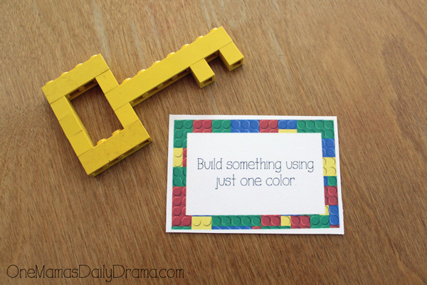"a challenge card that reads ""Build something using just one color"" next to a yellow key made from bricks"