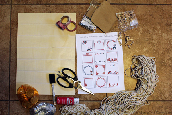 a pile of craft supplies including scissors, washi tape, paint, clothespins, cotton cord, and an unfinished piece of wood