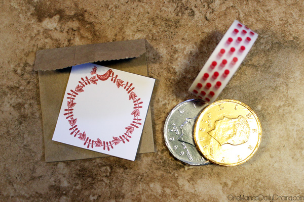 two chocolate coins, a paper card, a brown envelope, and a roll of red washi tape