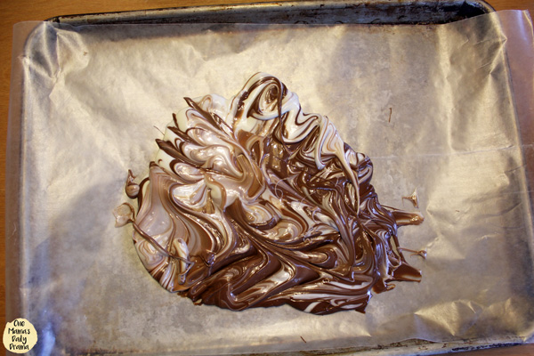 brown and white chocolate swirled together on a parchment-lined baking sheet