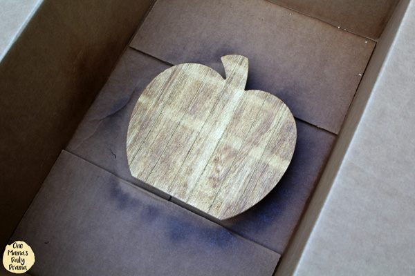 wood pumpkin cutout inside a cardboard box