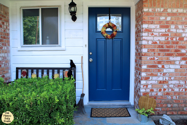 front porch with orange brick, white siding, and a blue door