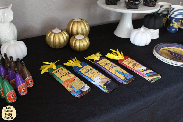 mini potion bottles and magic themed paper bookmarks on a black tablecloth