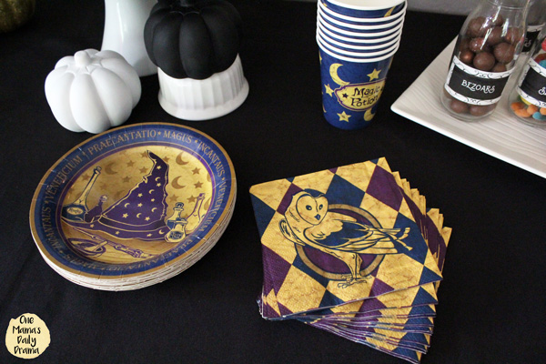 purple and gold wizard plates, napkins, and cups on a black tablecloth