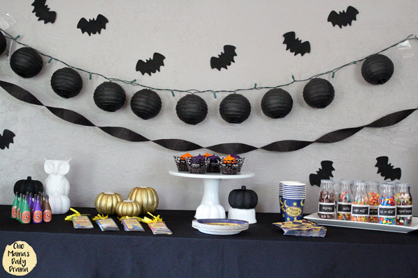 Halloween party tablescape with black bats, lanterns, and streamers, cupcakes, bottles of candy, and pumpkins