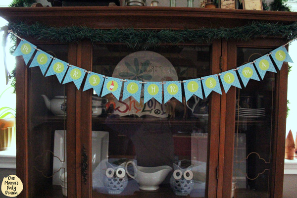 blue and green Christmas banner on a china hutch