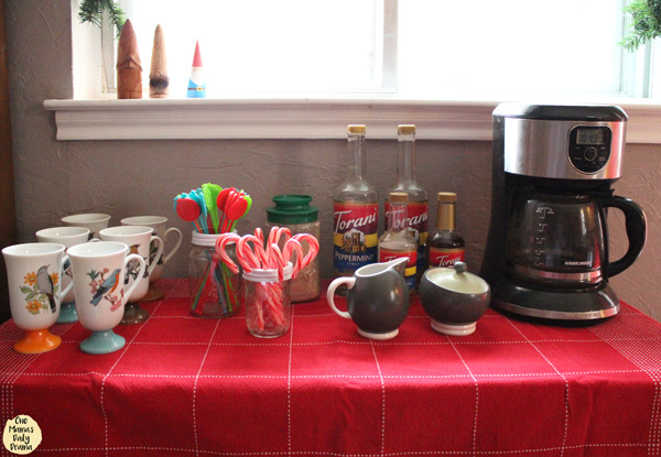 cocoa station with mugs, candy canes, stir sticks, flavored syrups, and a coffee maker