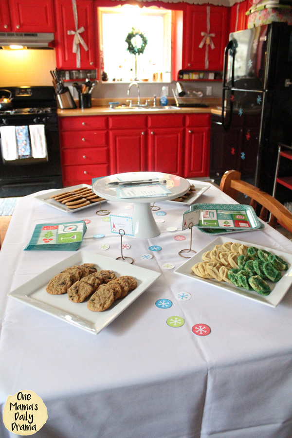 dining table with a white cloth set up with plates of cookies and a tray for voting ballots