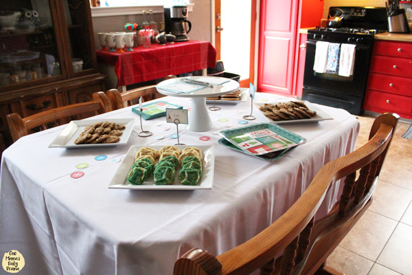 dining table with plates of cookies and a cocoa station in the background