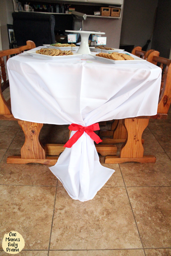 large white tablecloth on a small table with the excess fabric tied up with a red bow