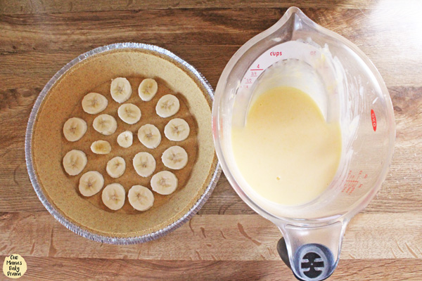 pie crust with sliced bananas next to a measuring cup full of pudding mix