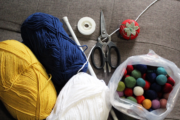 yellow, blue, and white yarn skeins, a bag of felt balls, a pair of scissors, and a tension rod sitting on a gray upholstered ottoman