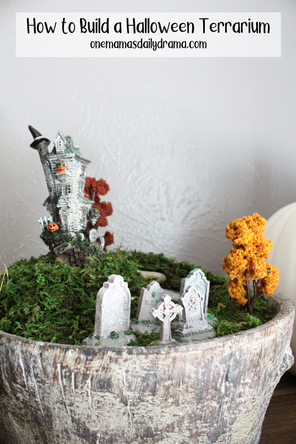 large resin container growing moss and decorated with a mini haunted house, faux trees, and tombstones