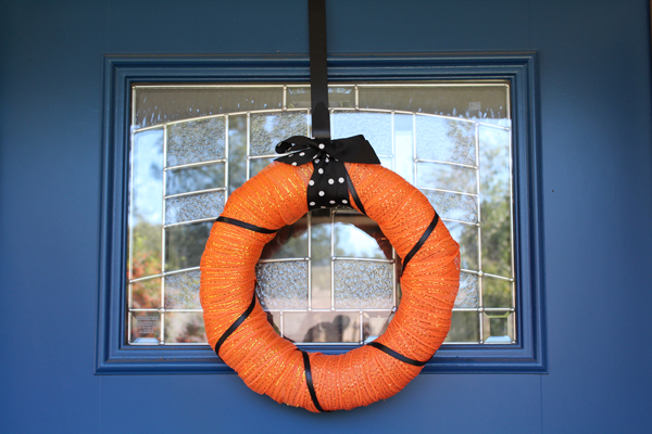 Orange wreath with black ribbons on a blue door / Halloween porch decor