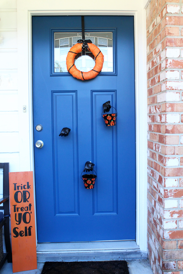 Black and orange Halloween porch / wreath, sign, and buckets of candy