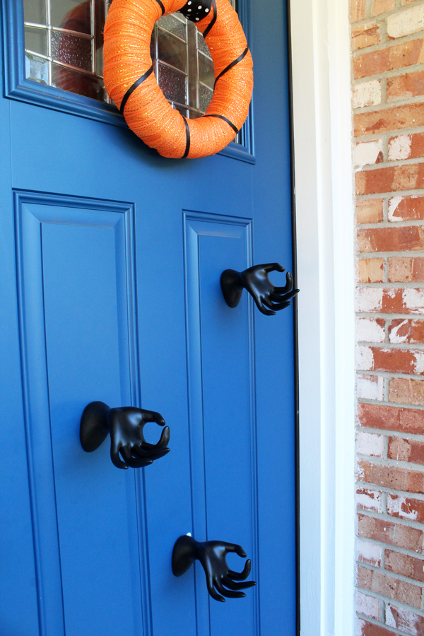 Attach mannequin hands to the door with outdoor Command strips