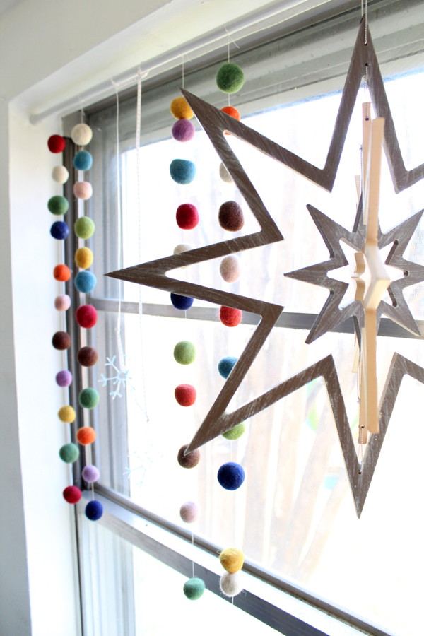 window with wooden stars, felt garland, and DIY snowflakes hanging from a tension rod
