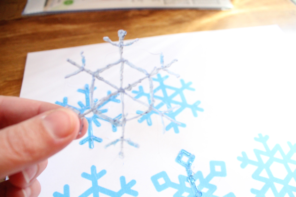 fingers holding a handmade snowflake with a paper template in the background