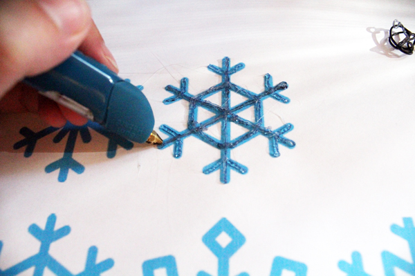 hand holding a 3Doodler and tracing a paper snowflake