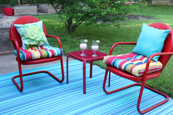 red patio chairs and cocktails sitting on a table outside