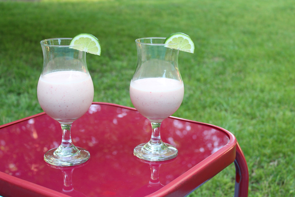 two clear glasses with pink shakes sitting on a table outside