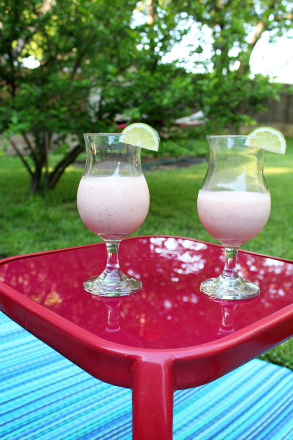 two drinks on a patio table with green landscaping in the background
