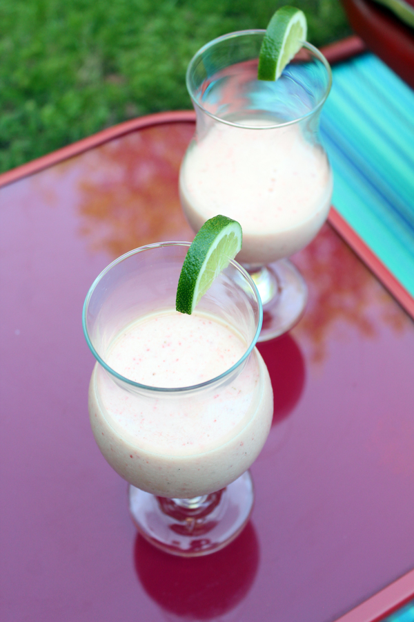 aerial view of two pink margarita shakes in hurricane glasses