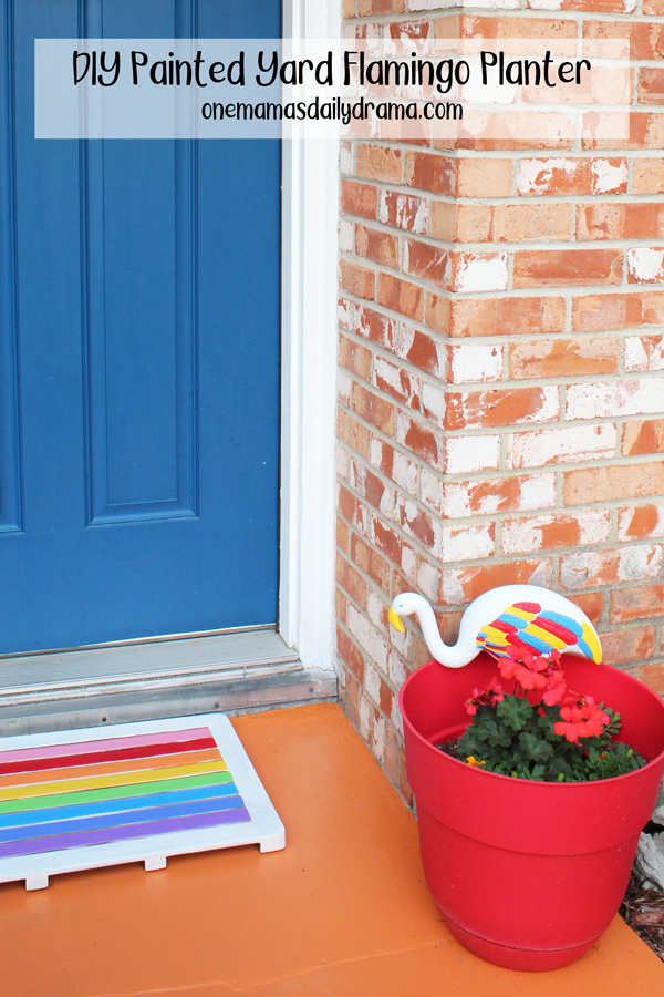 front porch with blue door, rainbow welcome mat, and red planter with painted flamingo