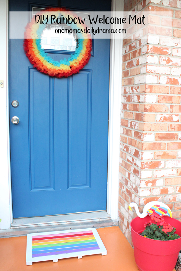 front porch with rainbow colored welcome mat, wreath, and potted plants