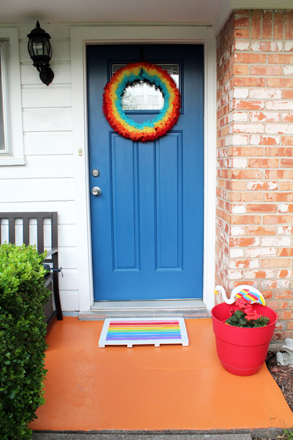 front porch with blue door, white siding, orange brick, and orange concrete