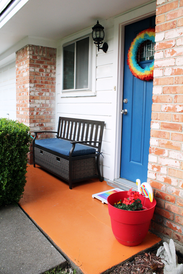 front porch with orange concrete, blue door, and rainbow accessories including a wreath, welcome mat, and planter