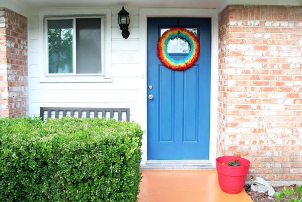 front porch with orange concrete, blue door, rainbow wreath, and red planter