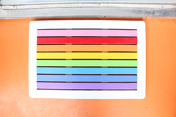 rainbow striped welcome mat on an orange porch